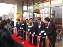 オープニングセレモニーでテープに挟みを入れるホクレン商事松浦祥文社長=右から5年目